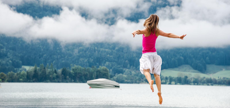La femme sautant au lac image stock