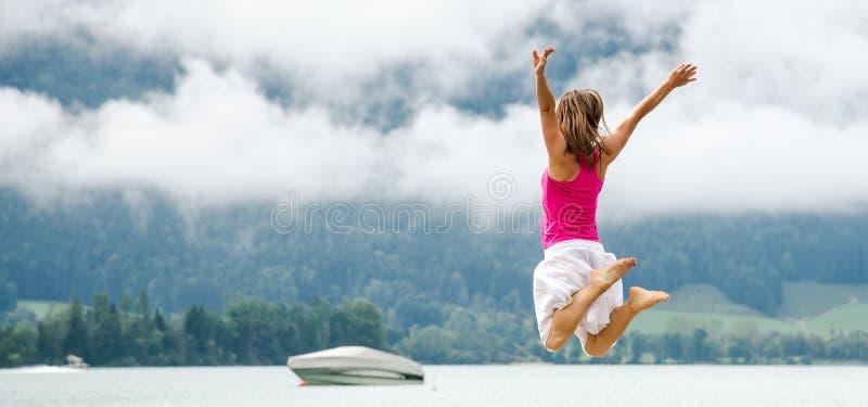 La femme sautant au lac images stock