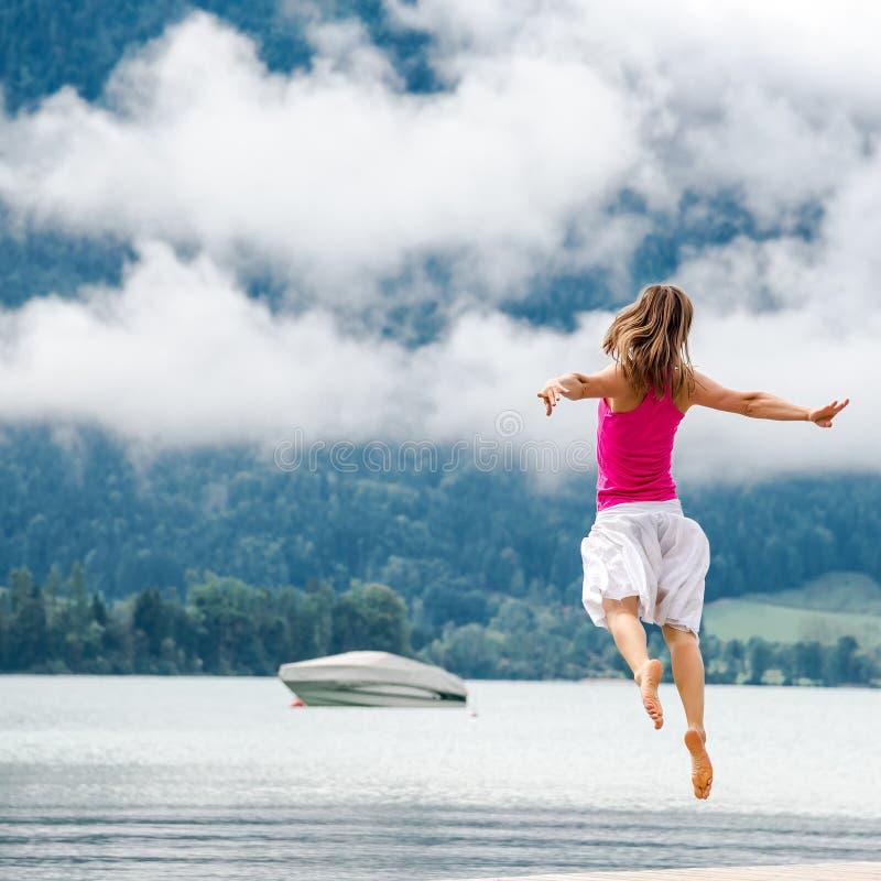 La femme sautant au lac photo libre de droits