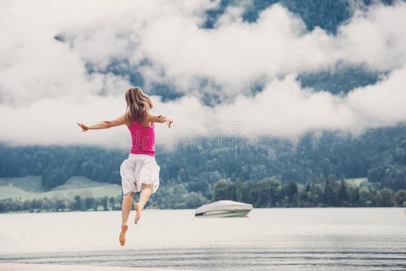 La femme sautant au lac photos stock
