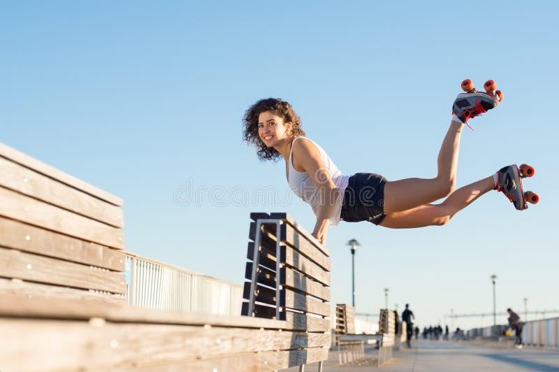 La femme sautant avec des patins de rouleau image stock