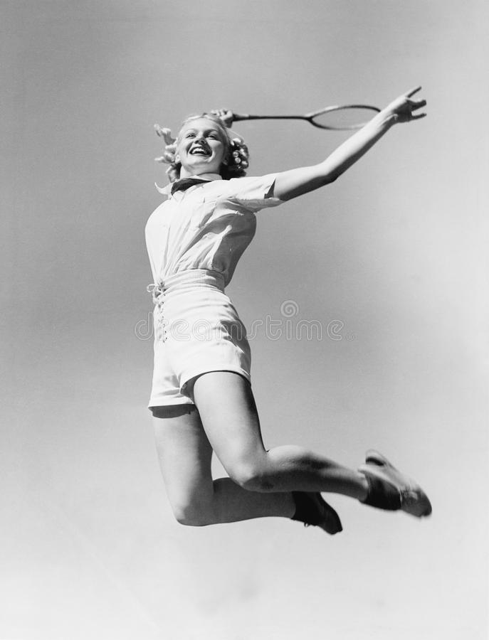 La femme sautant dans l'air avec une raquette de tennis dans sa main (toutes les personnes représentées ne sont pas plus long viv photos stock