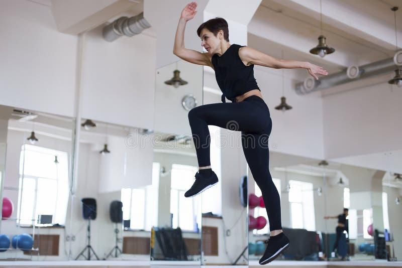 La femme sautant dans le gymnase, photo stock