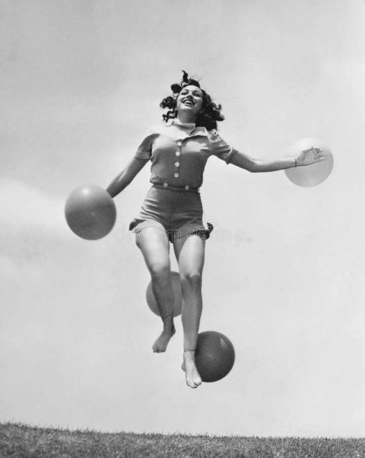 La femme sautant dehors avec des ballons (toutes les personnes représentées ne sont pas plus long vivantes et aucun domaine n'exi photo libre de droits