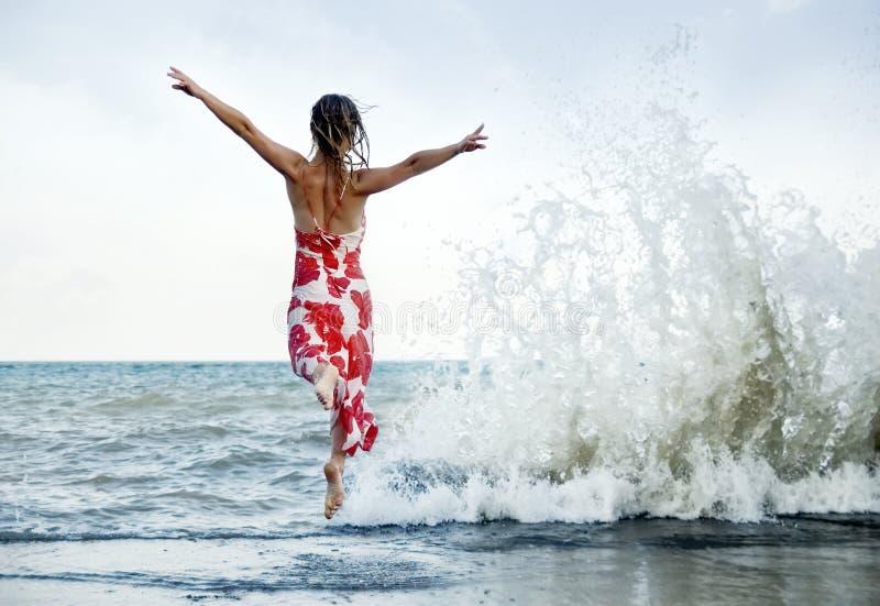 La femme sautant sur la plage image libre de droits