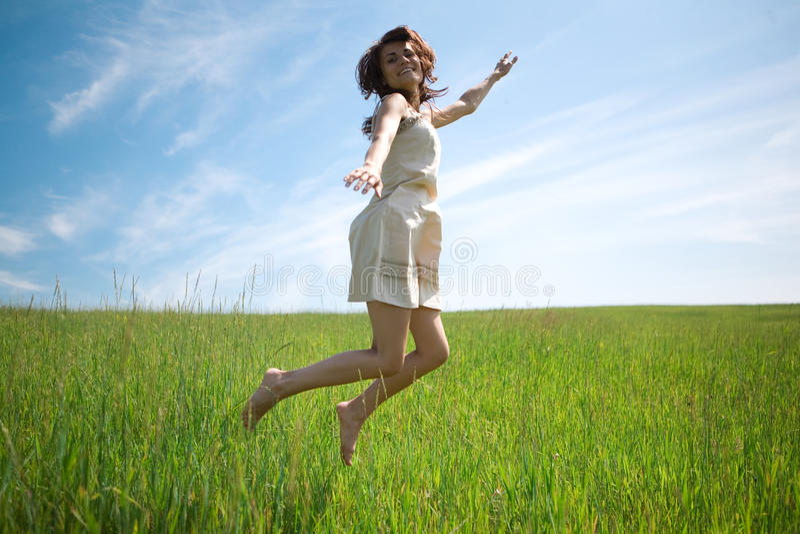 La femme sautent dans le domaine photo stock