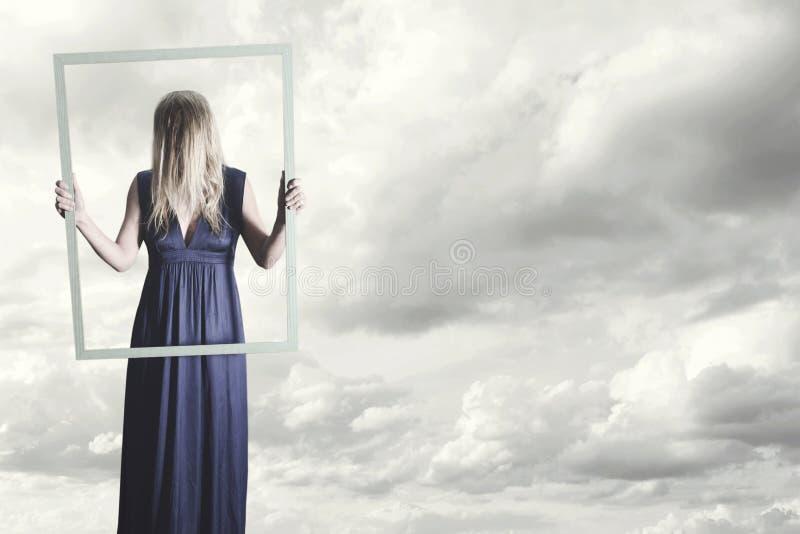la femme se montre dans le cadre d'une peinture avec ses cheveux couvrant son visage photos libres de droits