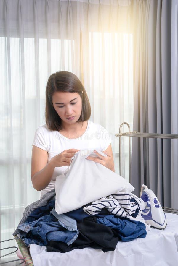 La femme se penche sur le bassin avec la blanchisserie et en regardant vêtez images libres de droits
