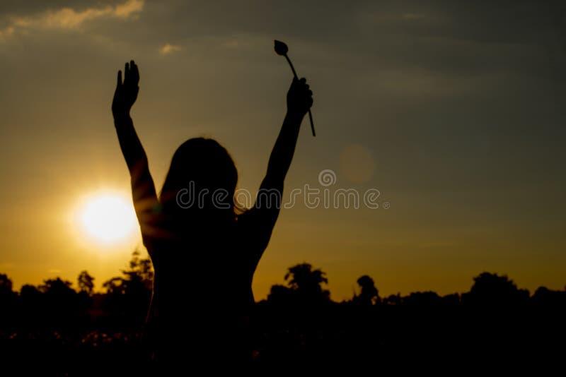La femme se tient au coucher du soleil heureusement image libre de droits