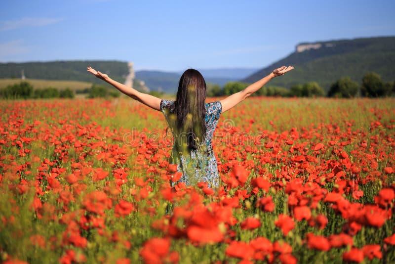 La femme se tient avec les bras ouverts sur le champ de pavot d'été image libre de droits