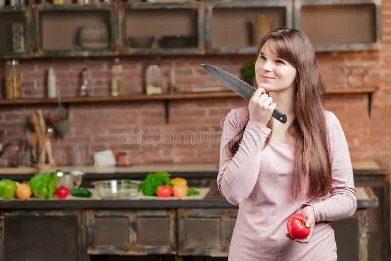 La femme se tient dans la cuisine près de la table avec les légumes frais la fille tient un couteau et une tomate dans des ses ma photographie stock libre de droits