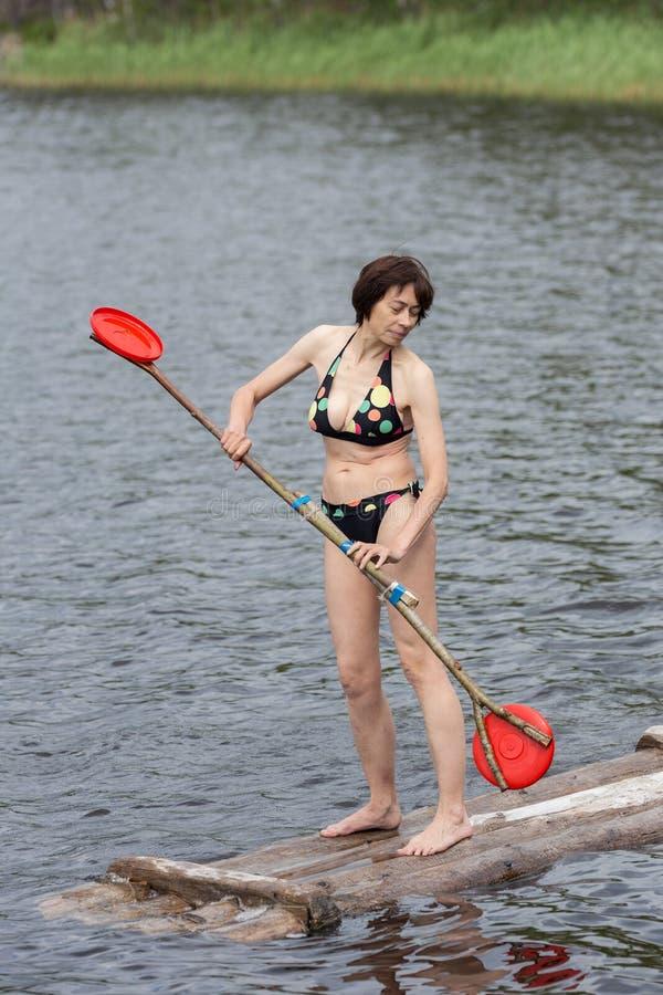 La femme se tient sur un radeau en bois photographie stock libre de droits