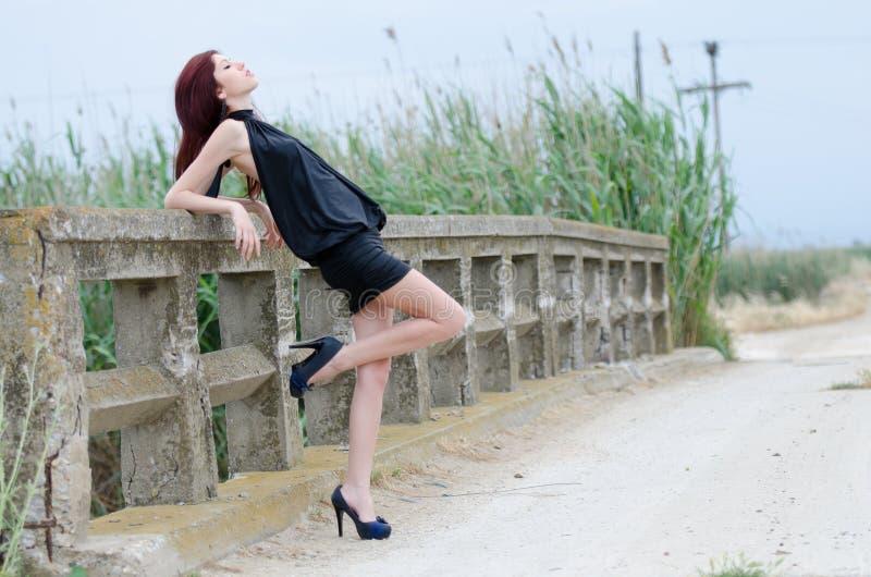 La femme se tient sur un vieux pont en ciment images libres de droits