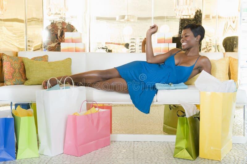 La femme se trouve avec des paniers dans des places assises de magasin photo libre de droits