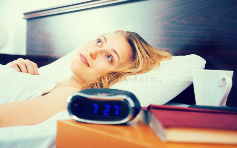 La femme se trouve sur le lit avec des yeux ouverts dans la chambre à coucher près de l'horloge et du livre image stock
