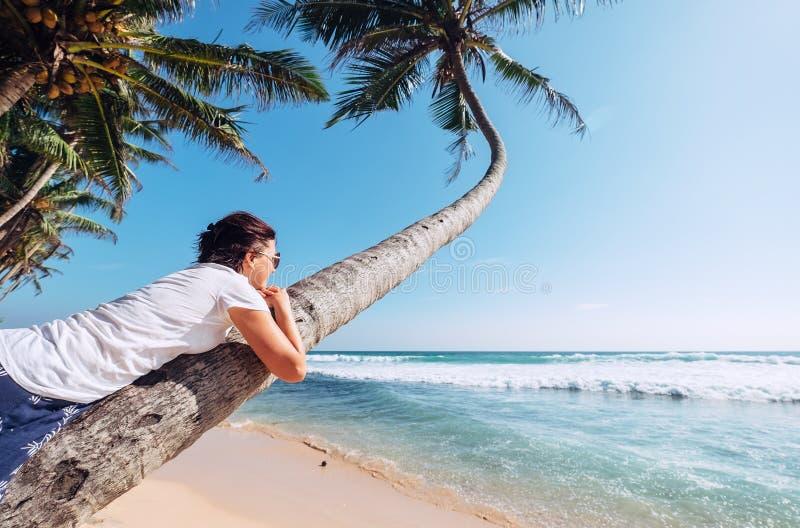 La femme se trouve sur le palmier et regarde ocaen dessus des vagues Été VCA image libre de droits