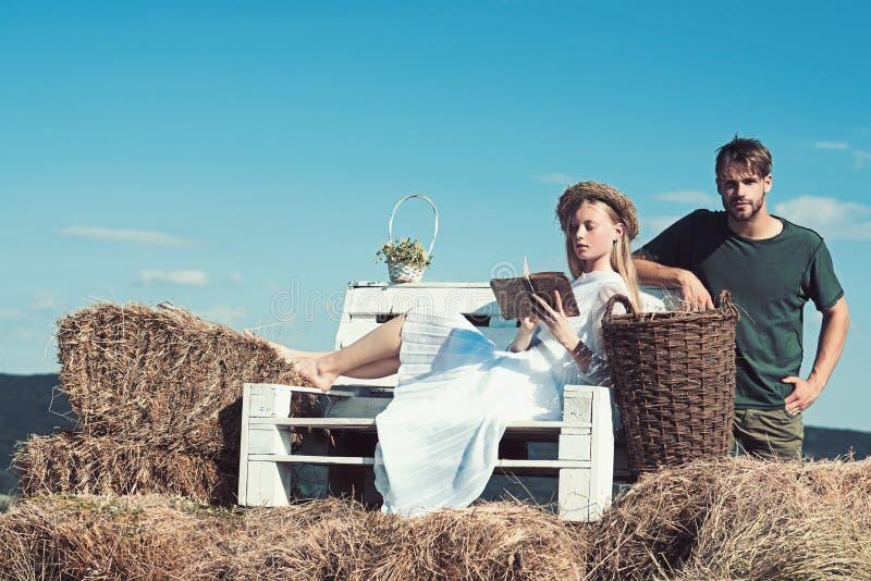 La femme sensuelle a lu le livre pour l'homme La jeune mariée de femme dans la robe de mariage détendent sur le banc Couples dans image libre de droits