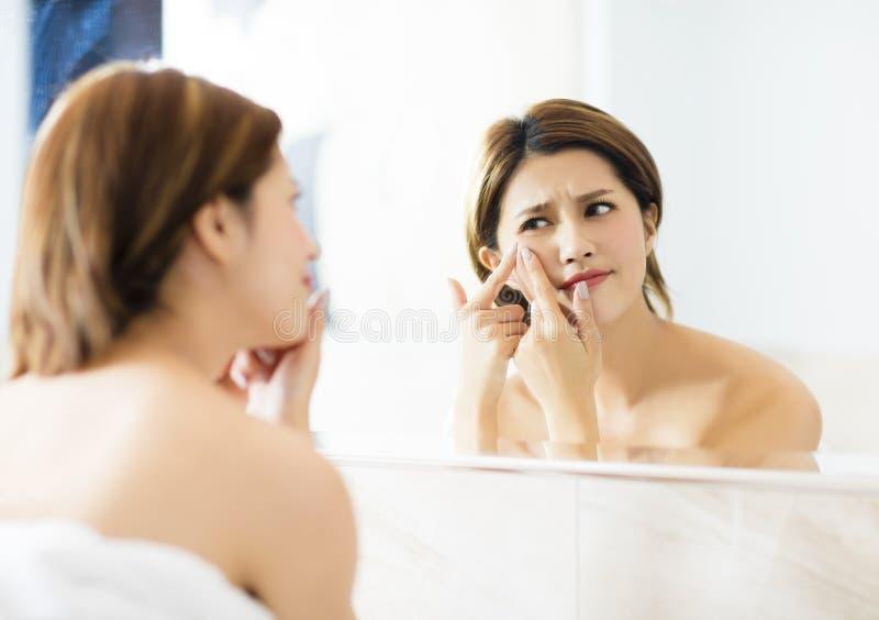 La femme serrent son acné devant le miroir images libres de droits