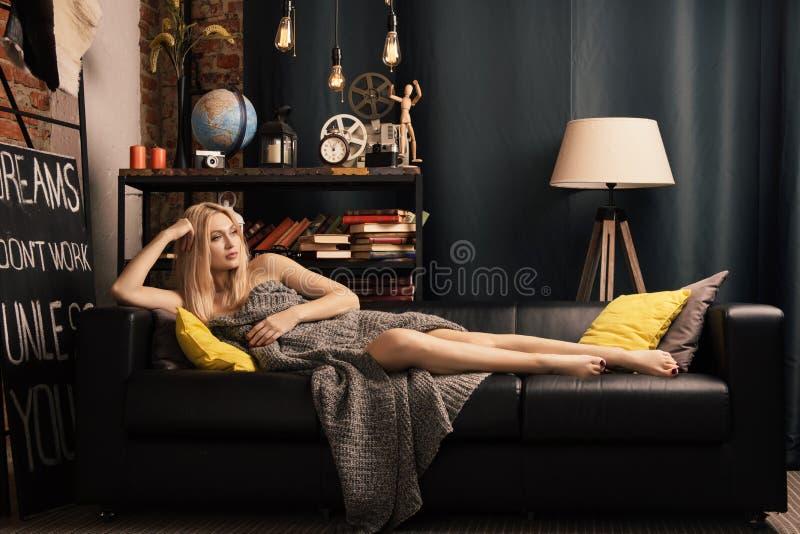 La femme seule se trouvant sur un sofa en cuir s'est transformée en couverture de laine photos stock