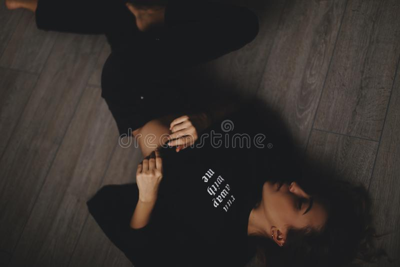 La femme sexy attirante se trouve sur le plancher Elle regarde la sensualité La fille chaude porte le regard noir total images stock