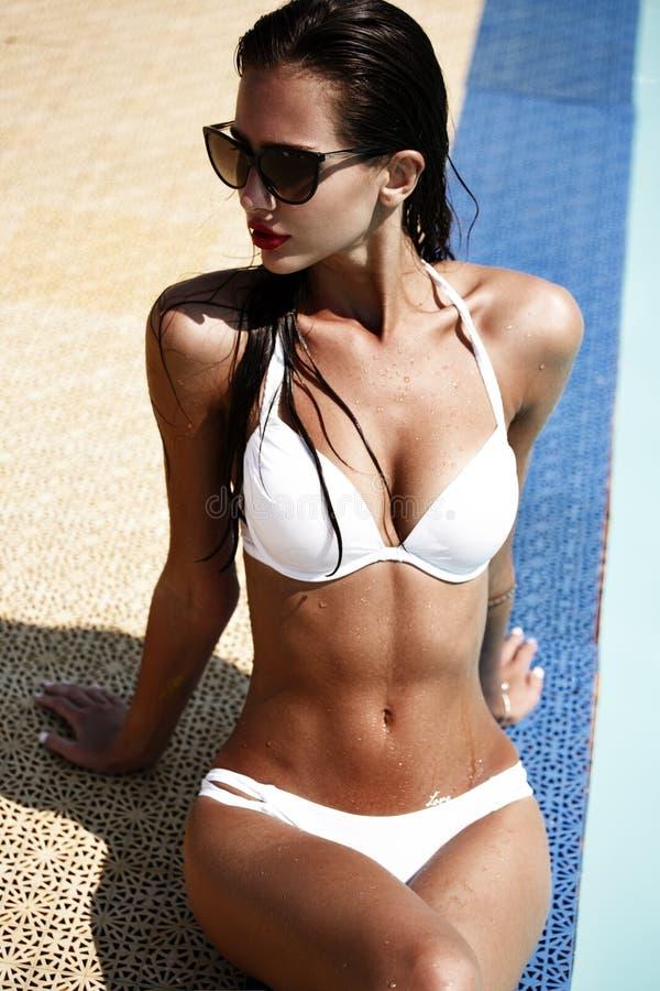 La femme sexy dans le maillot de bain blanc sur le corps mince et bien fait bronzé est se reposante et prenant le prend un bain d image libre de droits