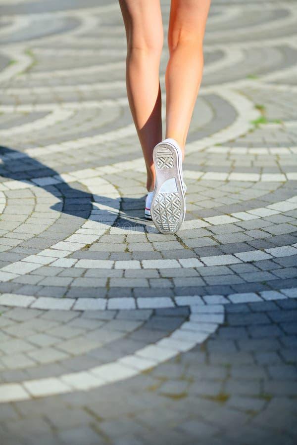 La femme sexy de jambes aux chaussures en caoutchouc vont en pavant des tuiles photos stock