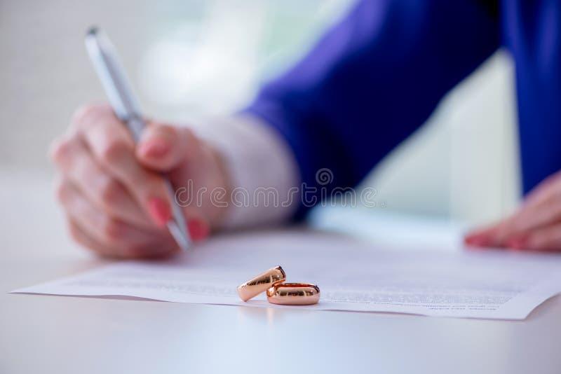 La femme signant l'accord prénuptial devant le tribunal image stock