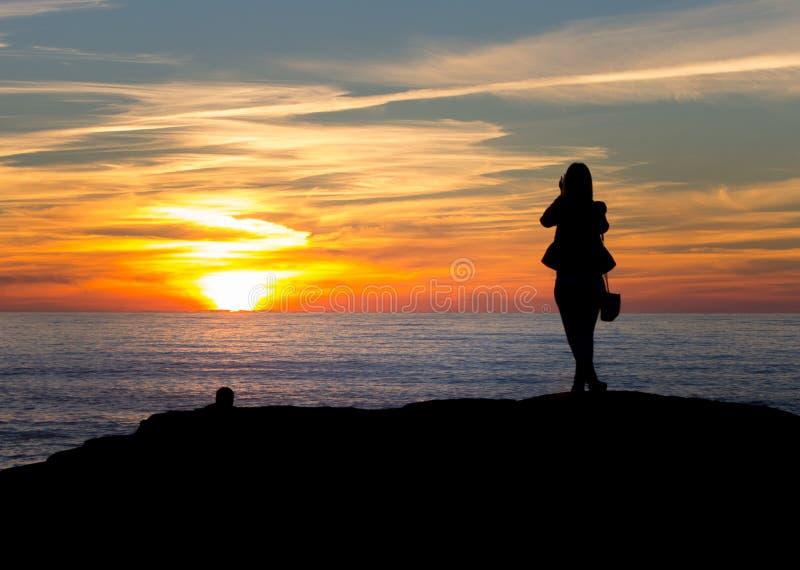 La femme silhouettée prend la photo du coucher du soleil image stock