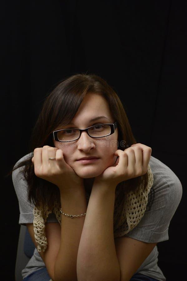 La femme songeuse philosophique en verres considère et pense avoir photographie stock libre de droits