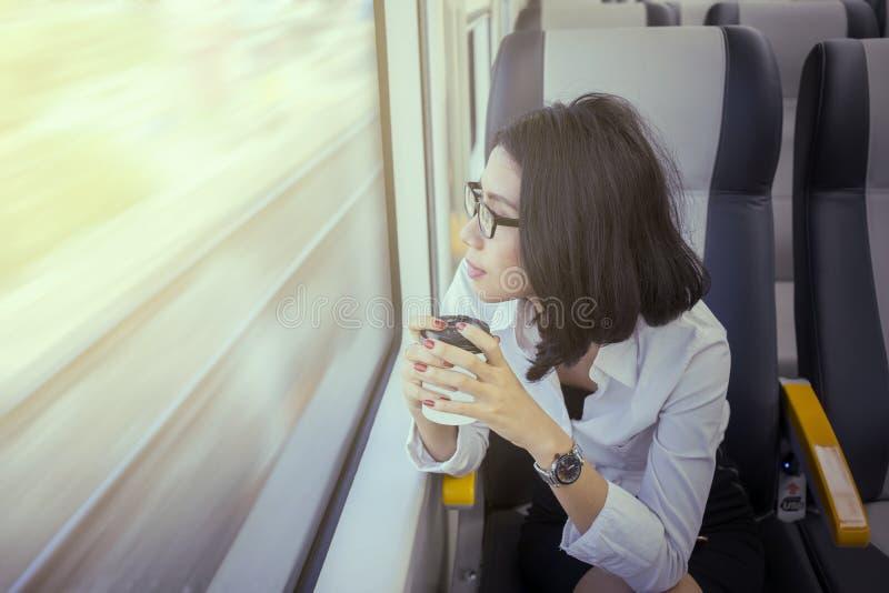 La femme songeuse tient le café dans le train d'aéroport image stock
