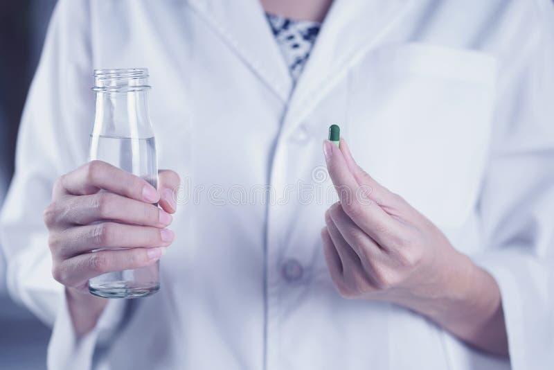 La femme sont prenante et mangeante des médecines et des vitamines pour l'aide en difficulté et saine image stock