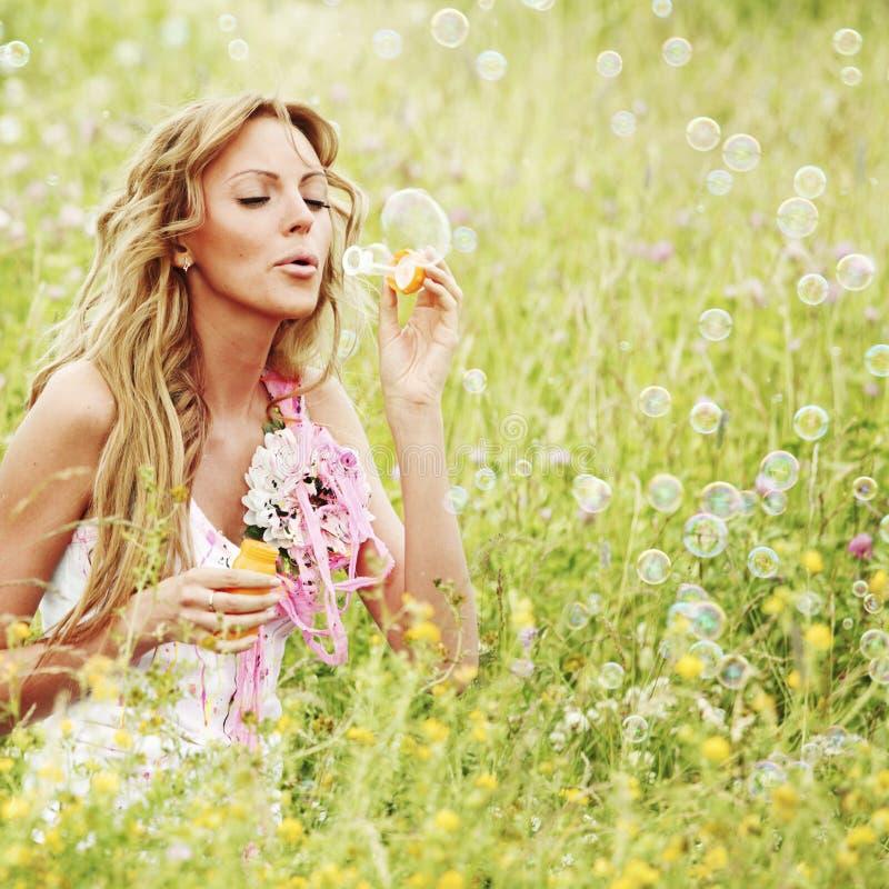 La femme souffle des bulles de savon photos stock