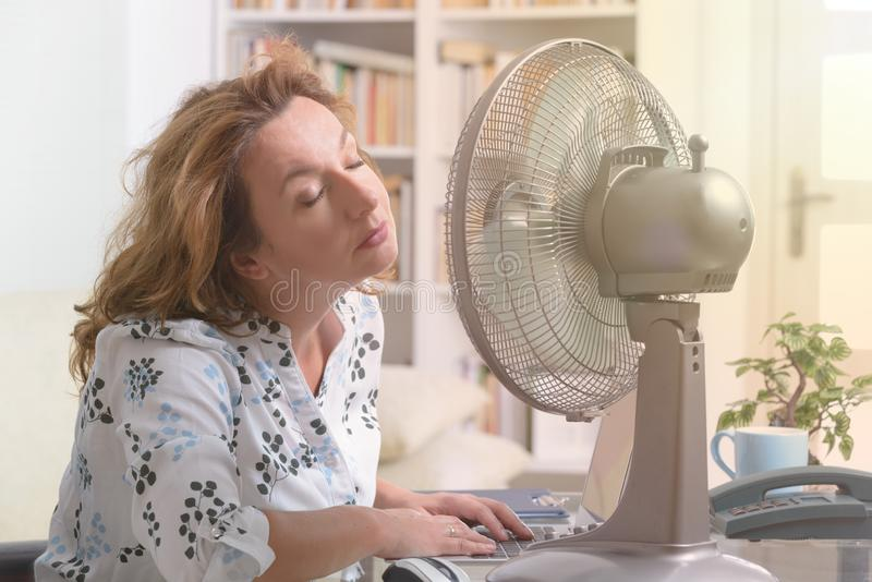 La femme souffre de la chaleur dans le bureau ou à la maison photographie stock libre de droits