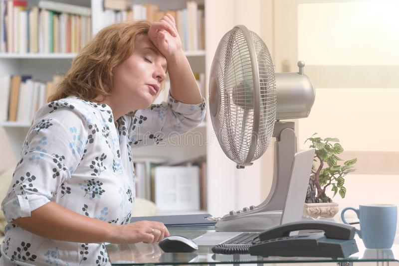 La femme souffre de la chaleur dans le bureau ou à la maison photos stock