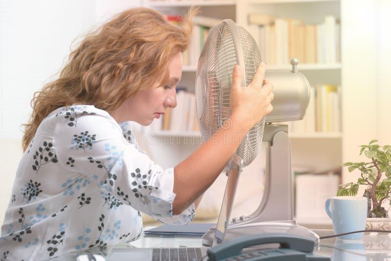 La femme souffre de la chaleur dans le bureau ou à la maison image stock