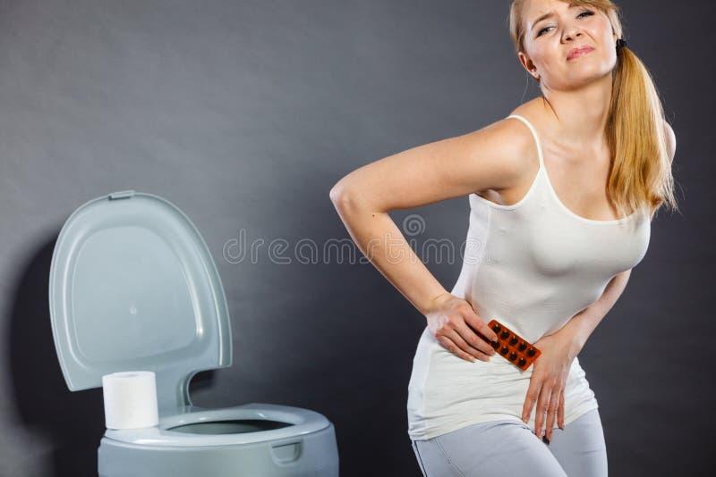 La femme souffrent de la douleur de ventre tient des pilules dans la toilette image stock
