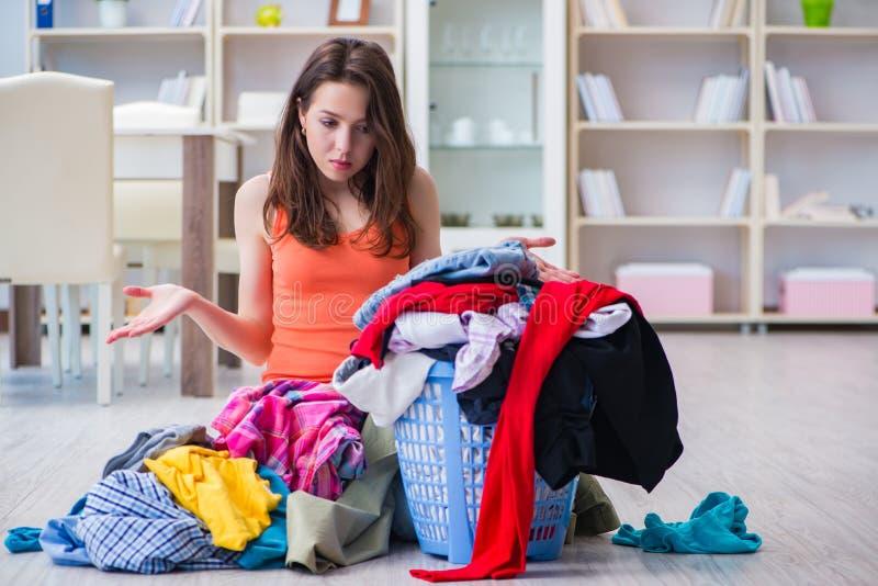 La femme soumise à une contrainte faisant la blanchisserie à la maison images libres de droits
