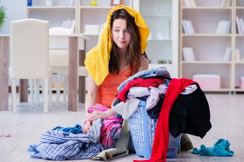 La femme soumise à une contrainte faisant la blanchisserie à la maison photo stock