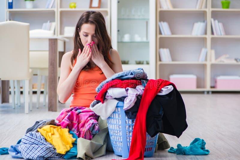 La femme soumise à une contrainte faisant la blanchisserie à la maison photographie stock