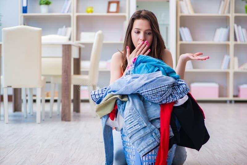 La femme soumise à une contrainte faisant la blanchisserie à la maison photographie stock libre de droits