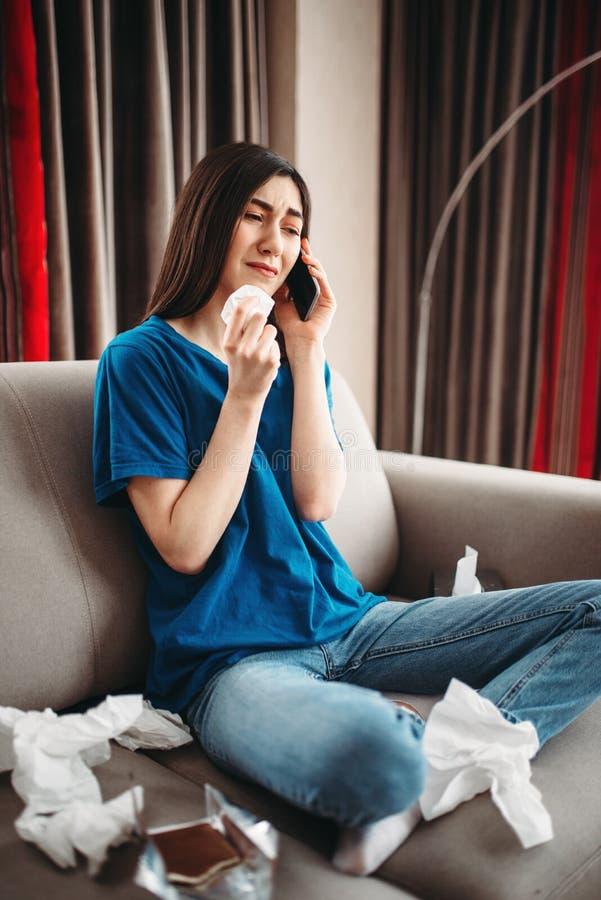 La femme soumise à une contrainte s'asseyant sur le divan et mange du chocolat image libre de droits