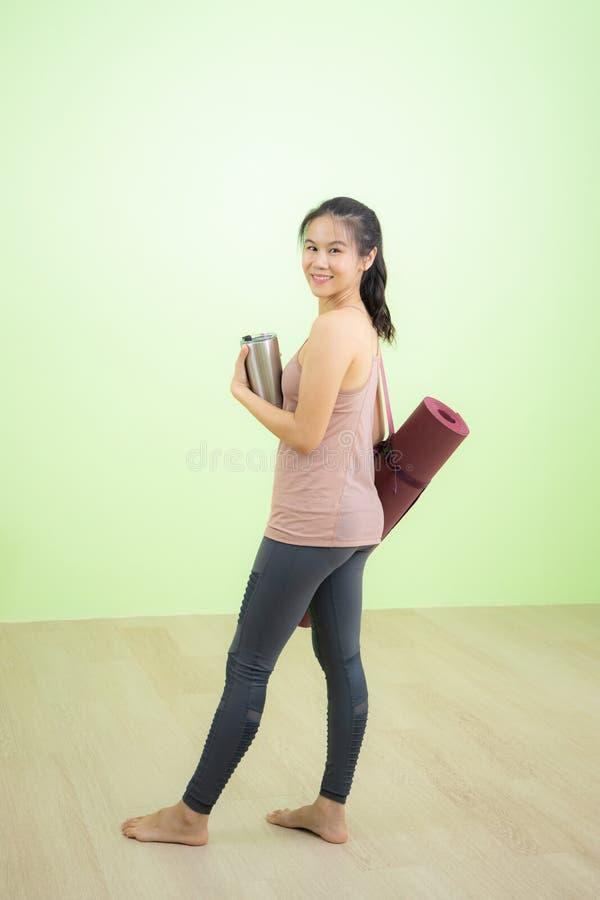 La femme sourit heureusement dans le studio de yoga photographie stock