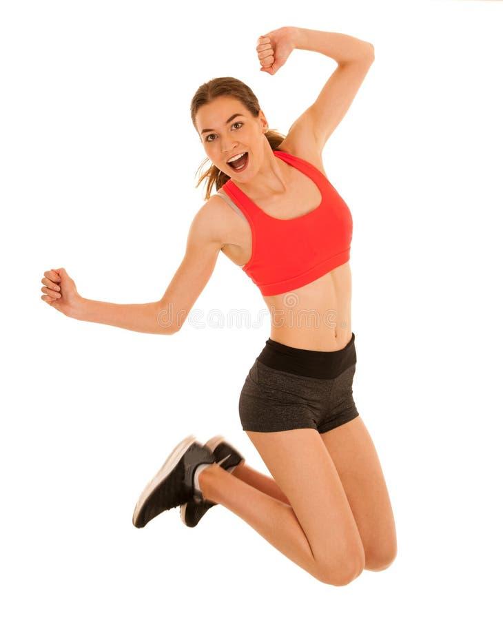 La femme sportive attirante saute islated au-dessus du fond blanc photo libre de droits