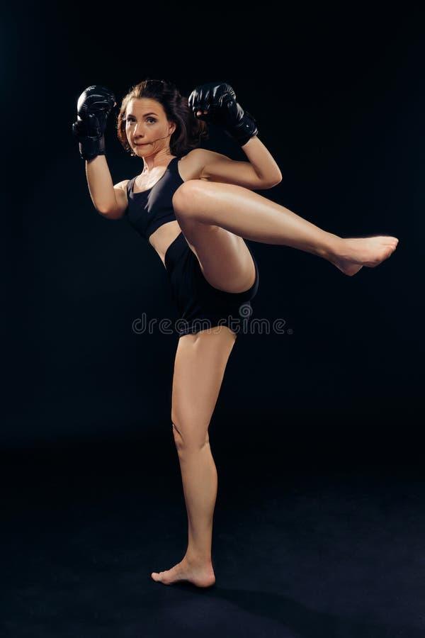 La femme sportive dans des gants de boxe pratique le karaté dans le studio photo stock