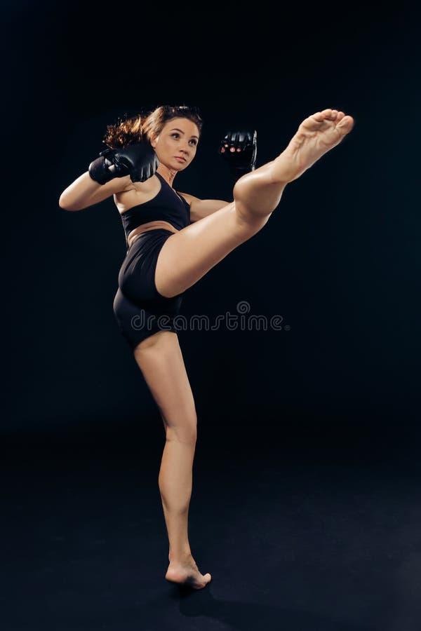 La femme sportive dans des gants de boxe pratique le karaté dans le studio image libre de droits