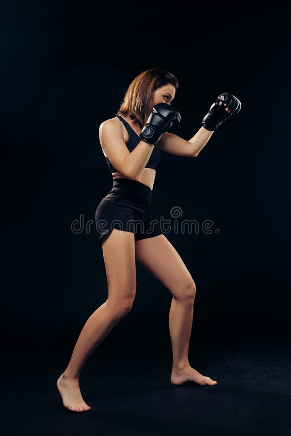 La femme sportive dans des gants de boxe pratique le karaté dans le studio photo libre de droits