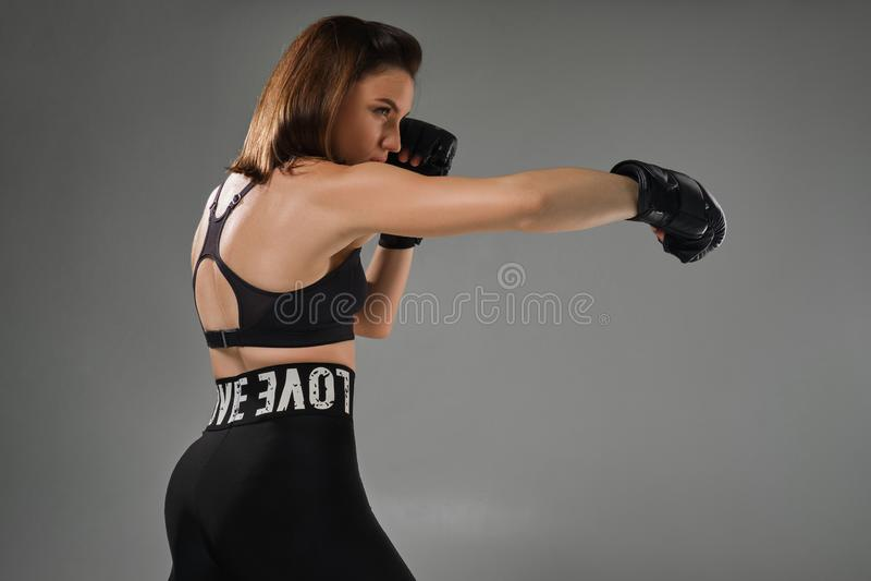 La femme sportive dans des gants de boxe pratique le karaté dans le studio images libres de droits