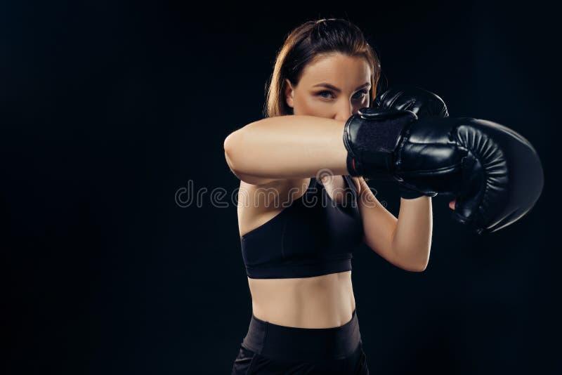 La femme sportive dans des gants de boxe pratique le karaté dans le studio photographie stock libre de droits
