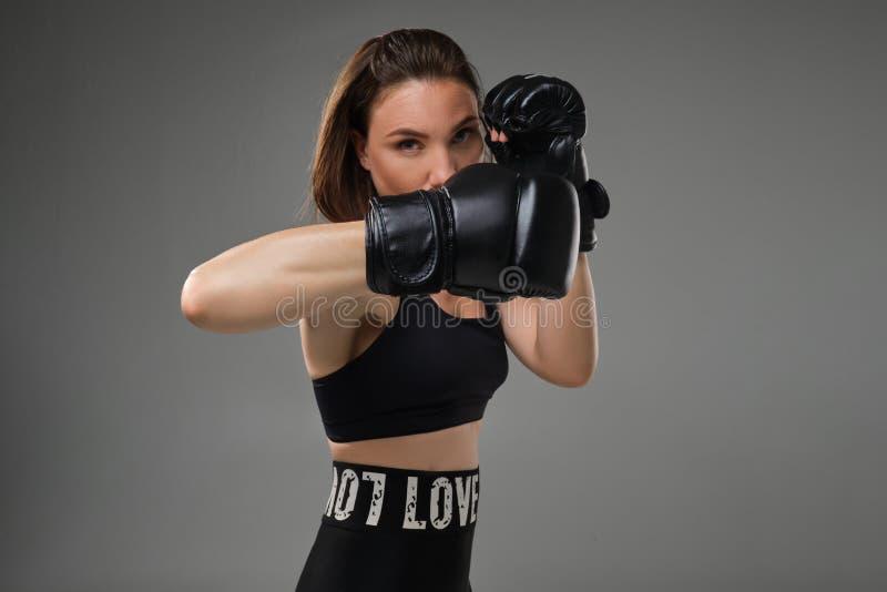 La femme sportive dans des gants de boxe pratique le karaté dans le studio images stock