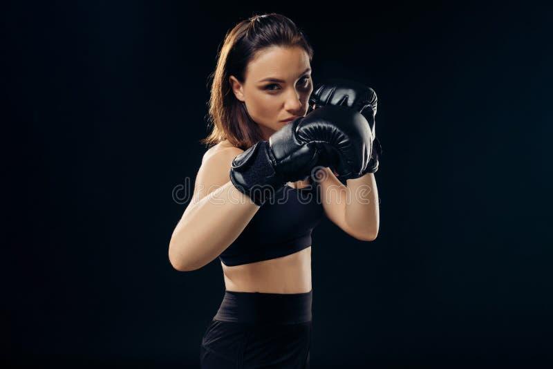 La femme sportive dans des gants de boxe pratique le karaté dans le studio photographie stock